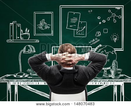 Back view of young businessman in suit relaxing in creative drawn office on chalkboard background