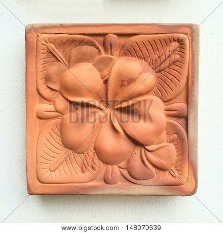 Carve clay a flower on white wall.