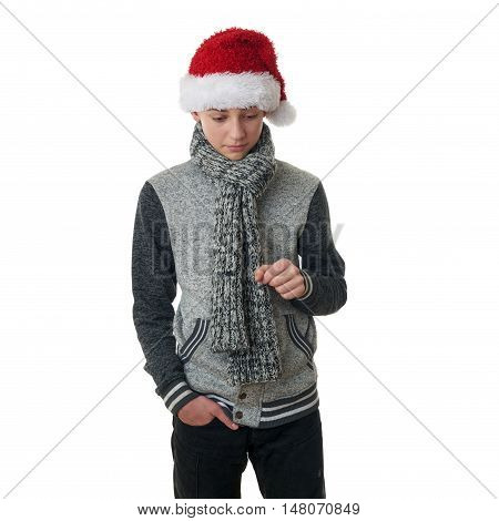 Cute teenager boy in gray sweater and christmas hat loking down over white isolated background, half body