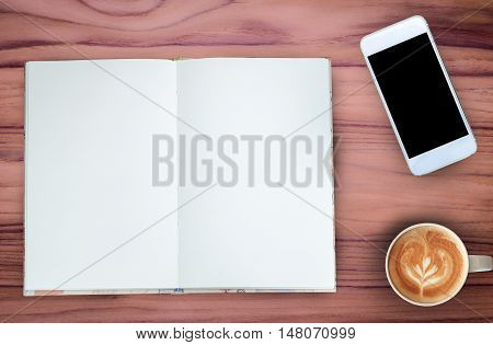 Coffeenotebook and mobile phone on teak wood texture background.