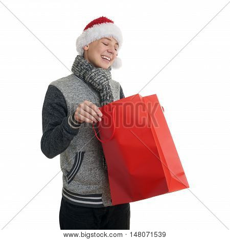 Cute teenager boy in gray sweater and christmas hat looking into red shopping bag over white isolated background, half body