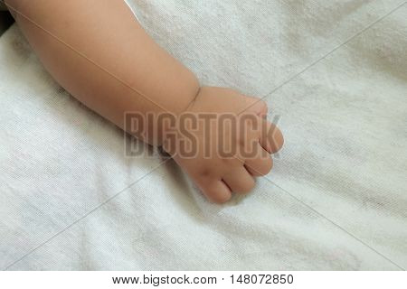 New born baby hand on white bed