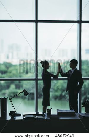Business people celebrating success in office, focus on foreground