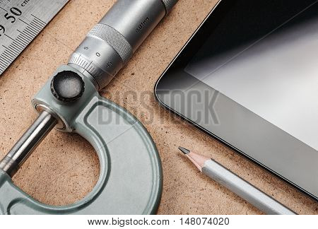 Part of the workplace with a tablet ruler pencil and micrometer