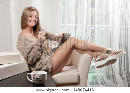 Young Woman On Sofa Shopping Online With Debit Card