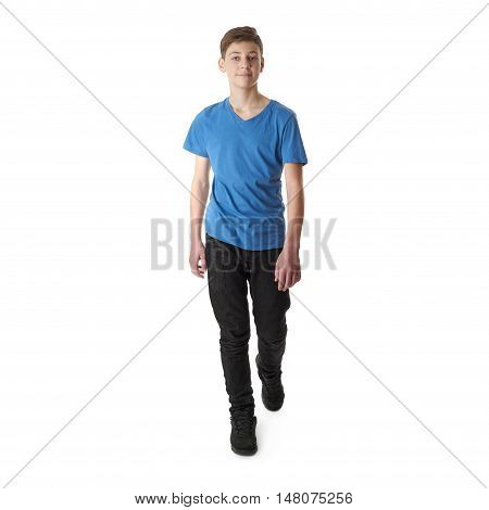 Cute teenager boy in blue T-shirt stepping over white isolated background full body