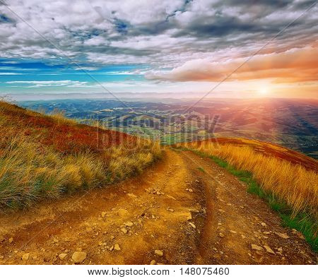 Country road in the mountains at sunset. Road leading down