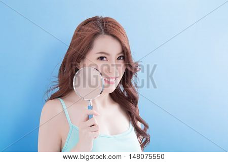 beauty woman take magnifying smile to you with blue background asian