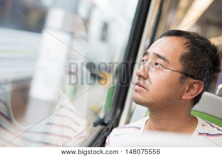 man looking out the window and take the subway in Hong Kong