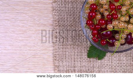 Berries in a vase. Polviny vase with berries. Currants in a glass bowl. Red white currants in a vase on a woven fabric.