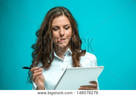 displeased young business woman with pen and tablet for notes on a blue background