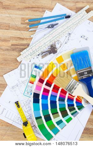 Interior designer's working table with energy rating chart, architectural plan of the house, color palette and brushes, top view