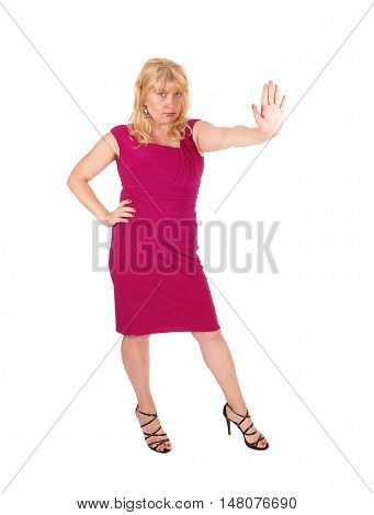 A tall blond woman in a red dress standing from front holding her hand up and say's stop isolated for white background.