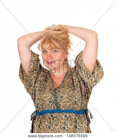 A portrait image of a pretty blond woman in a dress with her hands on her head isolated for white background.