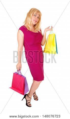 A pretty woman in her forties holding up the shopping bag's standing in high heels isolated for white background.