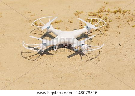 White quadrocopter on sand, close-up. New unmanned aerial copter in dessert. Electronics innovation. Modern Technologies. Aeromodelling