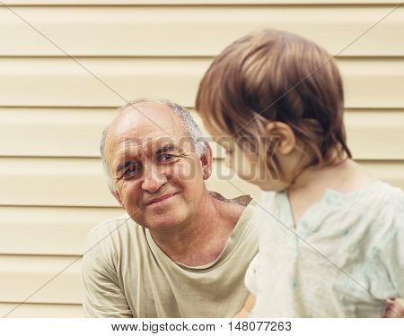 Toned portrait of Happy granddfather and grandaughter playing at yard