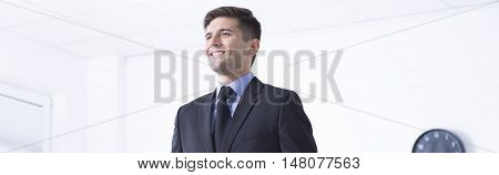 Young man in a suit is standing and looking ahead