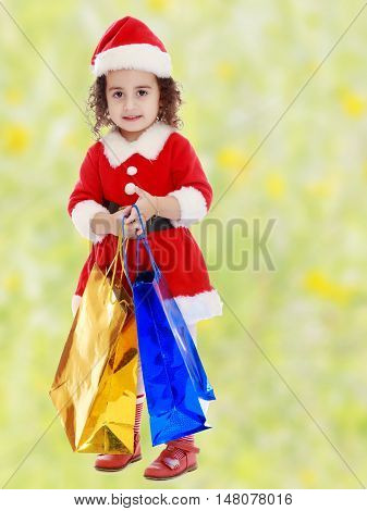 Adorable little curly-haired girl in a coat and hat of Santa Claus, holding colorful shopping bags.Bright, floral yellow-green blurred background.