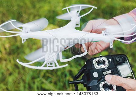 Operator holding remote control and drone. Unmanned aerial copter for photo and video starting in forest. Aeromodelling, hobby, leisure concept