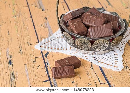 Vase with chocolate candies on openwork napkin on old wooden table.