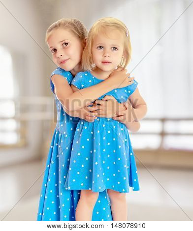 Two charming little girls, sisters , in identical blue dresses with polka dots , cuddling.