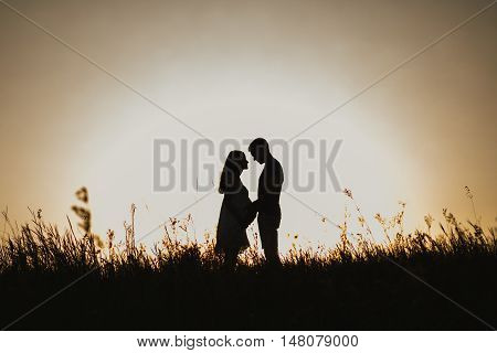 Silhouette of pregnant lady and husband. Sunset