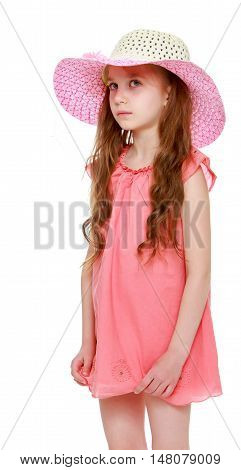 The doubting little girl with long pigtails to her waist and braided white bows. In short pink summer dress and pink hat. Standing sideways to the camera. Close-up - Isolated on white background