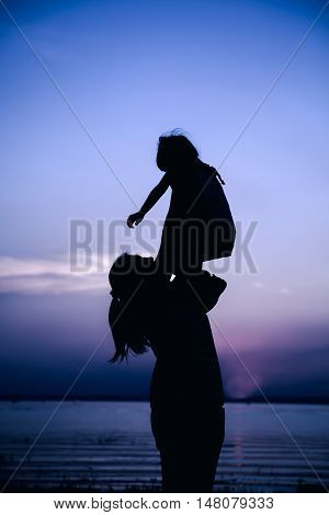 Silhouette Of Mother And Child Enjoying The View At Riverside.