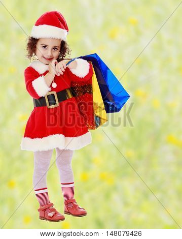 Caucasian little curly-haired girl in a coat and hat of Santa Claus carries on his shoulder a colorful shopping bags.Bright, floral yellow-green blurred background.
