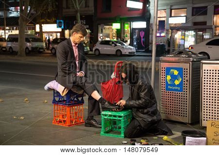 Melbourne, Australia - April 22, 2015: A business man getting his shoes cleaned in the streets of Melbourne
