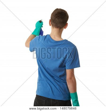 Cute teenager boy in blue T-shirt and green rubber gloves with spray tool over white isolated background from back, half body, cleaning concept