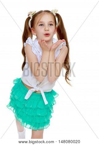 Cheerful little girl in a short green skirt and white shirt without any inscriptions . Long tails on the head in which braided white ribbons. Girl sends everyone a kiss. Close-up