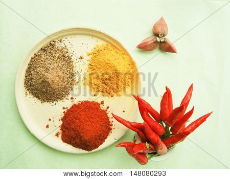 spices on a plate and red pepper
