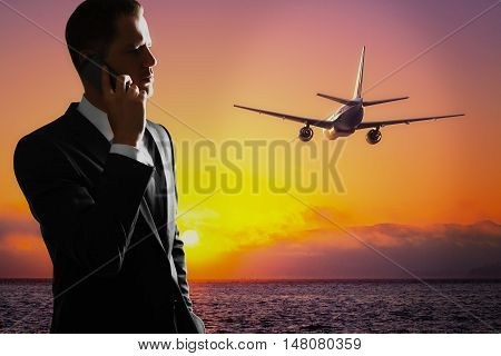 Young businessman talking on mobile phone on sea background with setting sun and flying by airplane. Freelance job concept
