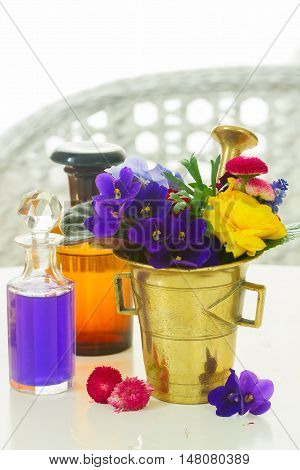 Fresh flowers, mortar and glass bottles of potions, herbal medicine