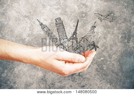 Male hand holding abstract sketch of landmarks and airplane on dark concrete background. Travel concept