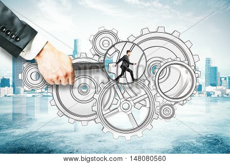 Hand holding magnifier over tiny businessman running on abstract cogwheel sketch. City background. Teamwork concept