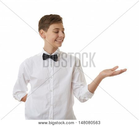 Cute teenager boy in white shirt and black bow tie holding something on palm over white isolated background, half body
