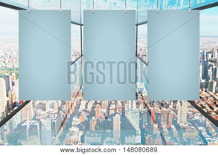 Three blank panels hanging in abstract transparent glass room with city view. Mock up 3D Rendering