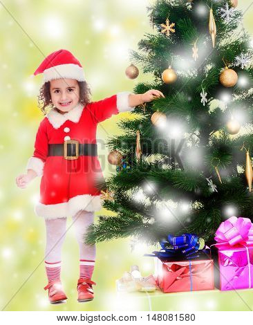Smiling curly-haired little girl, dressed as Santa Claus decorates a Christmas tree toys.On a green background with white snowflakes.