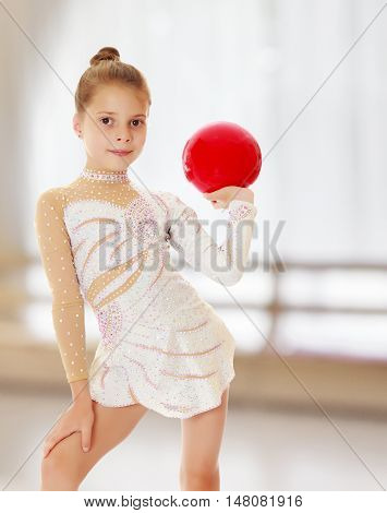 Beautiful little girl gymnast in elegant dress, posing with a red ball.On the background of the hall with large semi-circular window.