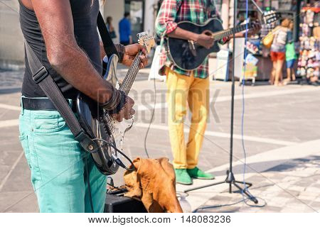 Black music street african performers playing electric guitar and bass at city square - Afro american colorful reggae musician artist with electric instruments close up scene - Bright day lights