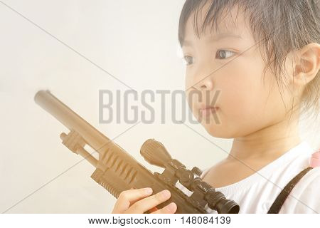 Asian child girl holding a gun filled with emotional commitment.