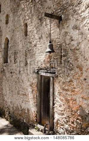 Old wooden door with a small bell above it in stone wall. Greece