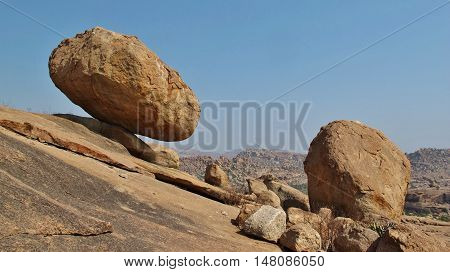 Big balancing granite boulder in Hampi India. Popular region for rock climbing. Unique landscape.