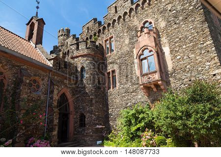 Reichenstein Castle Rhine Valley Germany - UNESCO World Heritage - courtyard : stone wall with windows tower balcony against blue sky