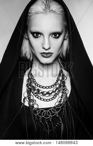beautiful fashion gothic girl with blond hair, black make up and piercing