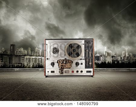 Old Reel Tape Recorder On View Of City In Stormy Sky