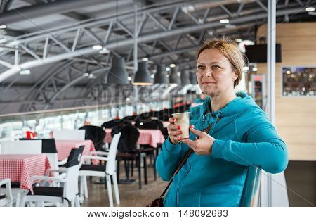 Caucasian woman standing with coffee at international airport while waiting for her flight. Female passenger at terminal.